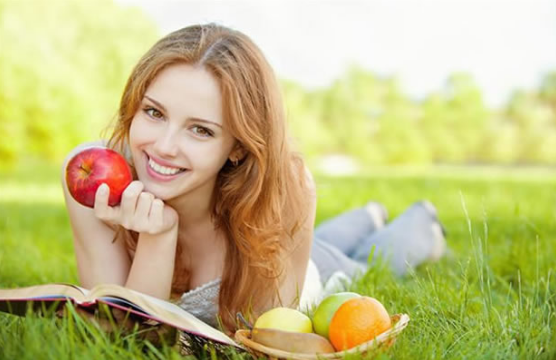 An Attractive Woman Reading In nature, Enjoying Healthy and Nutritious Apples and Oranges, Supplements 101